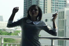 Happy businesswoman listening to music and dance on the  terrace in the cityNTSC Arkistovideo