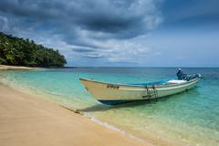 Little motorboat in the turquoise waters of Banana beach, UNESCO Biosphere Stock Photos