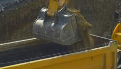 Excavator loading soil on a dump truck. Slow motion close up video. Stock Footage