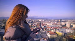 Browsing on smartphone with city scape in background 4K Stock Footage