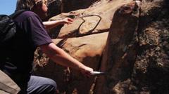 Man climbs up rock wall Stock Footage