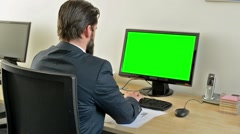 Young handsome man with full-beard (hipster) works on desktop computer in office Stock Footage