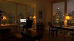one person working at home in high rise city apartment loft at night - stock footage