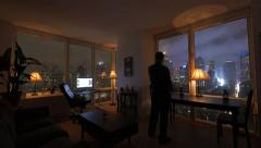 One person working at home in high rise loft apartment with city view Stock Footage