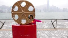 Little girl pose at avenue of the stars, with film reel sculpture Stock Footage