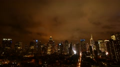 clouds moving over city skyline at night sky. urban building lights background - stock footage