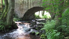 Stream flowing under the old stone bridge - stock footage