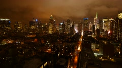 urban building lights background. clouds moving over city skyline at night sky - stock footage