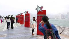 Young girl take pictures against stars on the avenue of the stars, HongKong Stock Footage