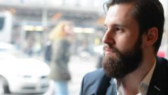 Young handsome man with full-beard (hipster) drinks coffee in cafe -urban street Stock Footage