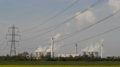 Power generating windmills by Drax coal powered power station yorkshire uk Stock Footage