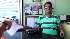 Portrait of Indian man with sunglasses sitting by a counter. Stock Footage