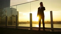 One businessman standing on rooftop at sunset talking on the phone Stock Footage