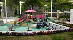 Children playground in park, panning around, evening time Arkistovideo