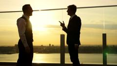 Sunset silhouette of two people talking together. business man meeting Stock Footage