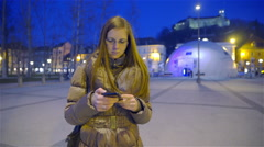 Woman busy typing on phone in city at night 4K Stock Footage