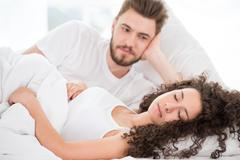 Husband admiring his sleeping wife Stock Photos