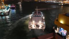 Catamaran ferry departs from night pier, slowly moving on water Stock Footage