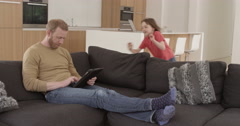Girl dives onto sofa to look at tablet with dad in contemporary modern home, in Stock Footage