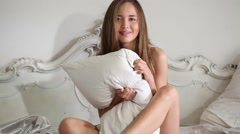 Cute and smiling girl gripping and throwing pillow - stock footage