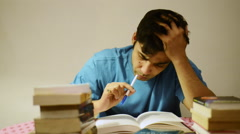 Stock Video Footage of Locked-on shot of a college student studying and looking tired at home