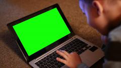 child (young boy) works on notebook - closeup laptop - green screen - stock footage