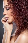 Profile view of a beauty with curly red hair Stock Photos
