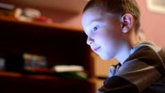 Child (young boy) plays game on tablet or notebook - lights glow on face Stock Footage