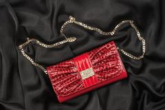 Red lacquer bag lying on a black silk - stock photo