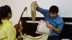 Slow motion shot of a couple pillow fight on bed Stock Footage