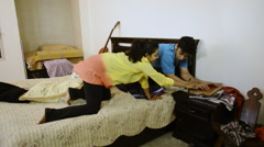 Locked-on shot of a couple pillow fight on bed Stock Footage