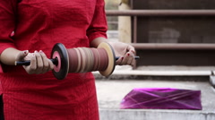 Locked-on shot of a woman holding kite thread roll on roof Stock Footage