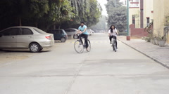 Tracking shot of a young couple riding bicycle Stock Footage