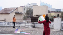 Slow motion shot of couple flying kite on roof Stock Footage
