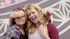 Two Teens Goof Around, Try To Cover Their Eyes And Mouths, They Laugh (4K) Stock Footage