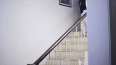 Slow motion shot of a schoolgirl moving down on staircase Stock Footage