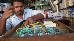 Portrait of Indian man standing by a counter and fixing wires. - stock footage