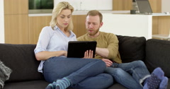 Attractive young couple in living room, look worried and stressed whilst Stock Footage