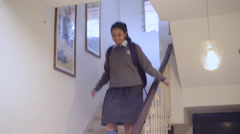 Locked-on shot of a schoolgirl moving down on staircase to going school Stock Footage