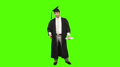 Man in graduation gown holding a diploma against green background Stock Footage