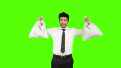Locked-on shot of a happy businessman holding money bags on green background Stock Footage