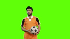 Locked-on shot of soccer player playing with a soccer ball on green background Stock Footage