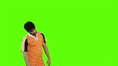 Locked-on shot of soccer player heading a soccer ball on green background Stock Footage