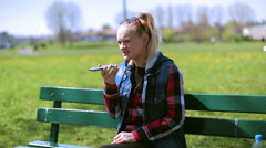 Angry woman sitting on the bench and talking on cellphone Stock Footage
