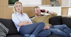 Handsome man chats on cell phone, annoying his girlfriend in contemporary home, - stock footage