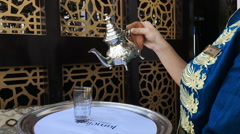 Woman pouring herbal tea into a glass, Dubai, United Arab Emirates Stock Footage