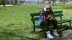 Girl wearing rollerblades and using cellphone in the park Stock Footage