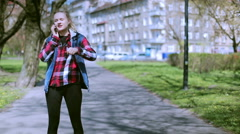 Stock Video Footage of Girl talking on cellphone and riding on rollerblades in the park