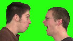 2 young men yelling at each other. Green background. - stock footage