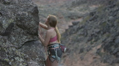 girl reaches for hold while rock climbing - stock footage